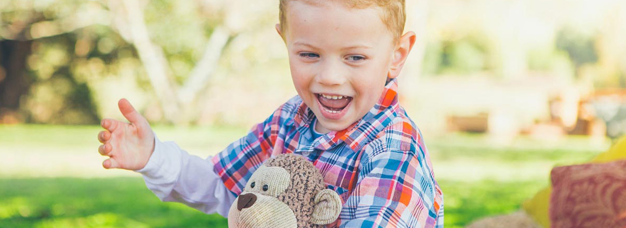 Kid Smiling with Teddy Bear